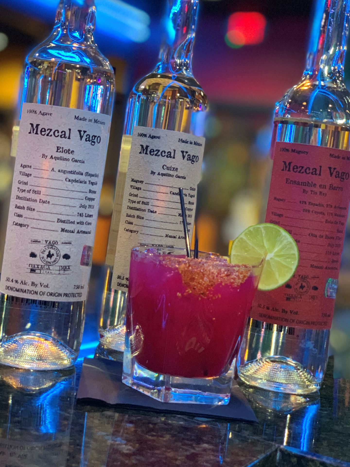Cocktail with a lime and stirrer in front of three bottles of assorted tequila