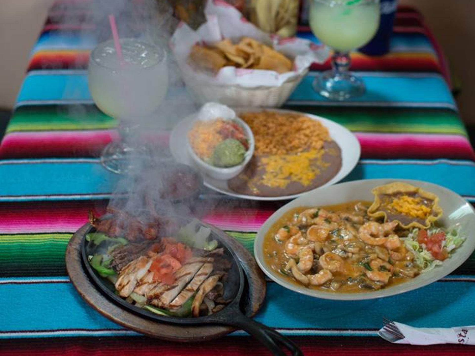 Multiple plates of assorted Mexican food on a table-top