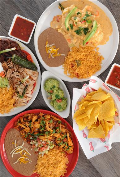 3 plates one has steak, grilled chicken with rice, one has wet burrito with rice and beans, one has chicken with rice and beans, side of chips with salsa and guacamole
