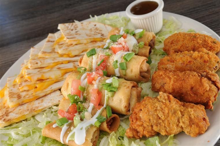 Sampler plater with taquitos dorados, flautas, inferno wings, jalapeno poppers, quesadillas with a side of sour cream and guacamole