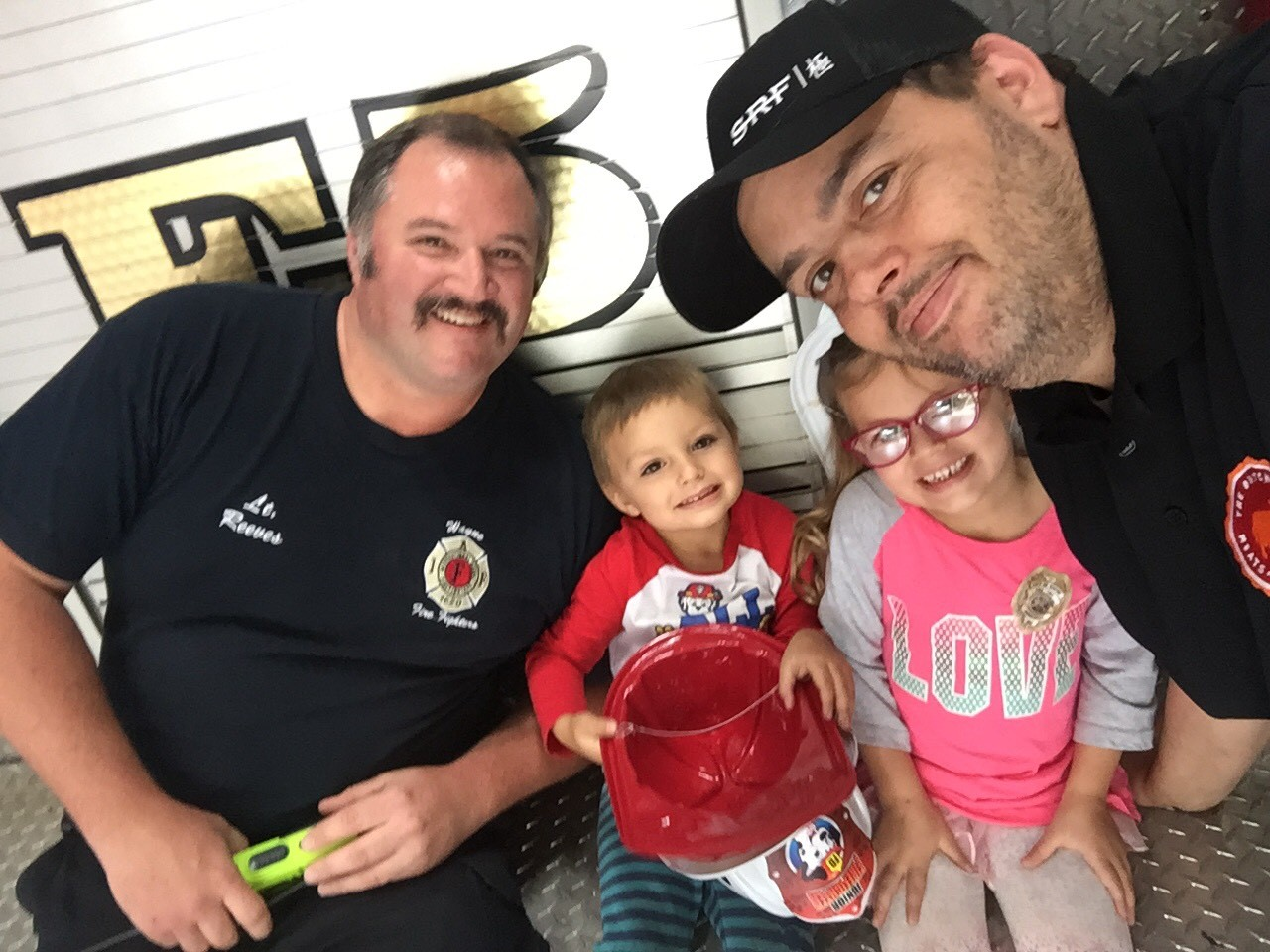 a selfie of two men and 2 kids smiling at the camera