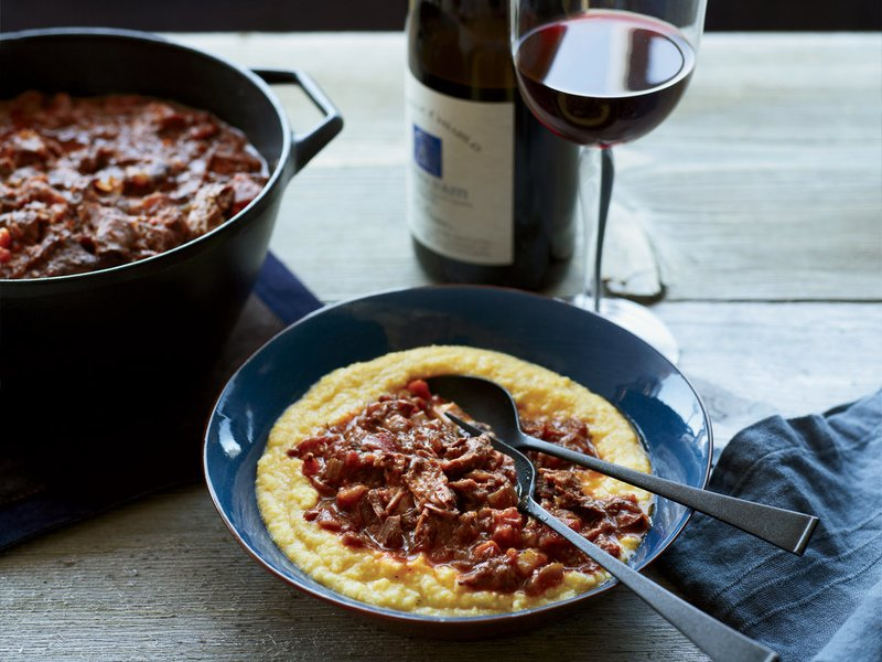 polenta with a shredded meat topping served with red wine