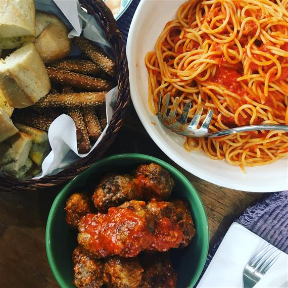 spaghetti and meatballs with bread and breadsticks