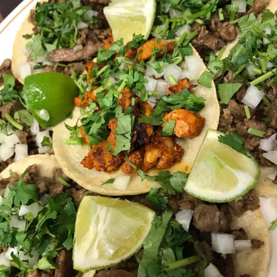 Chicken and steak street tacos with cilantro, onion and lime