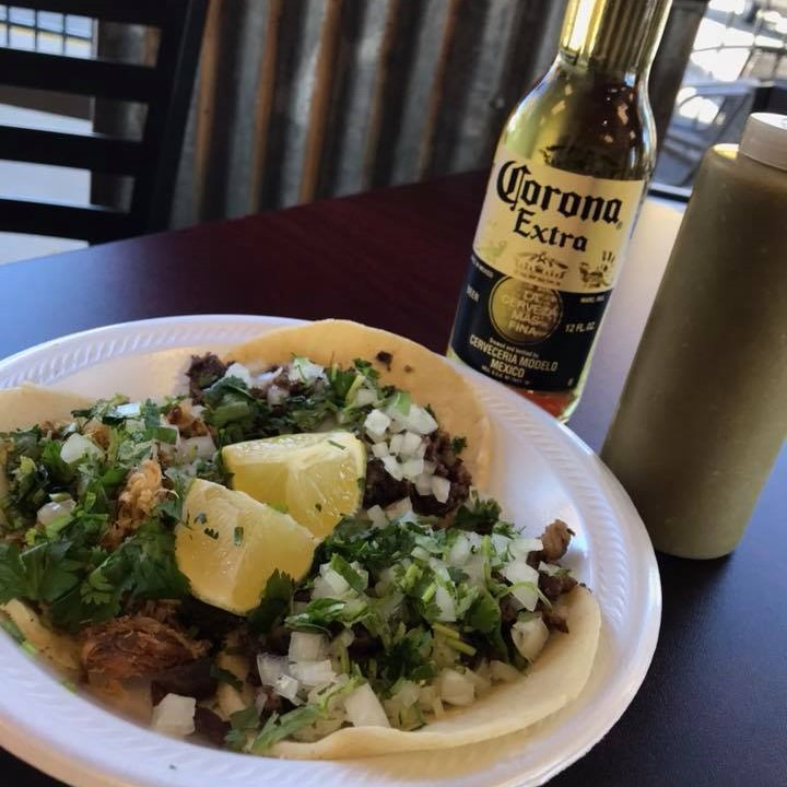 Three chicken street tacos with cilantro, onions and lime on a plate with a bottle of beer