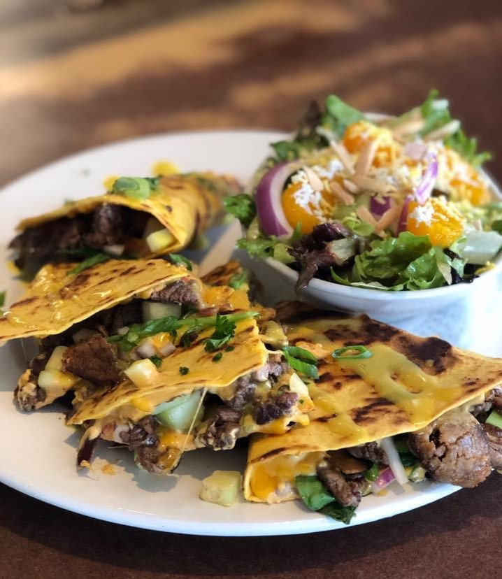 Steak quesadilla on a plate with a side salad