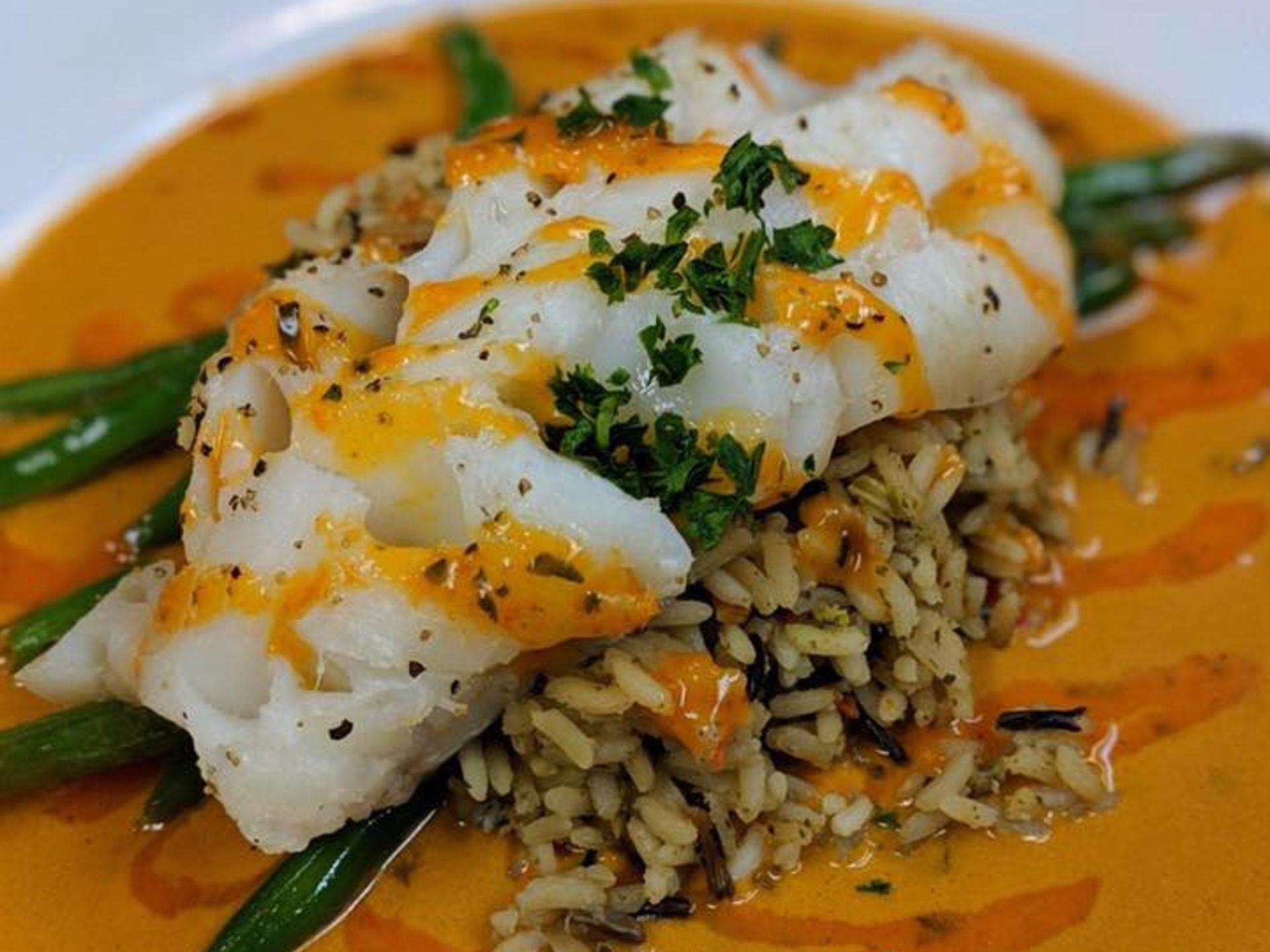 Cod with spicy sauce over rice pilaf and string beans