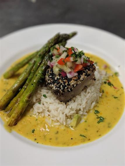 steak on a bed of rice over a yellow sauce served with fresh pico and roasted asparagus