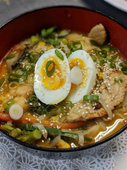 ramen with chicken slivers, vegetables, and hardboiled eggs and sesame seeds