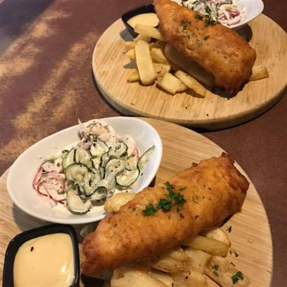 fish and chips on circled wooden boards with side salads and fries