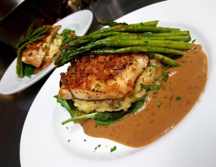 grilled chicken on a bed of mashed potatoes topped with asparagus
