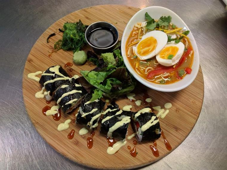 sushi on a circle board with soy sauce and a bowl of ramen