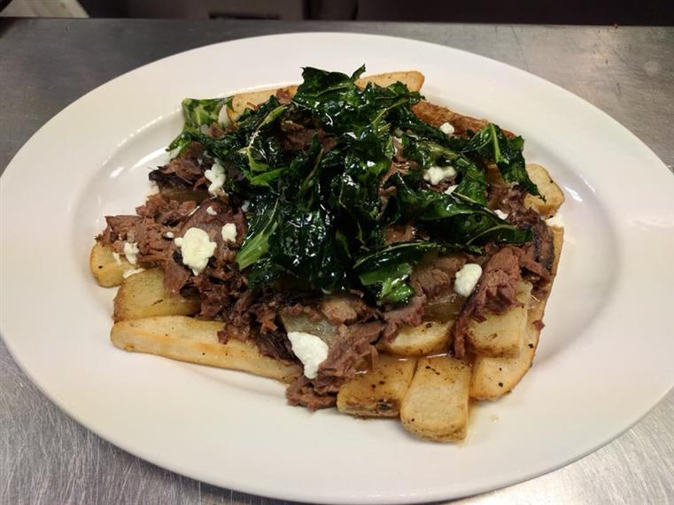 sliced meat on a bed of french fries topped with spinach