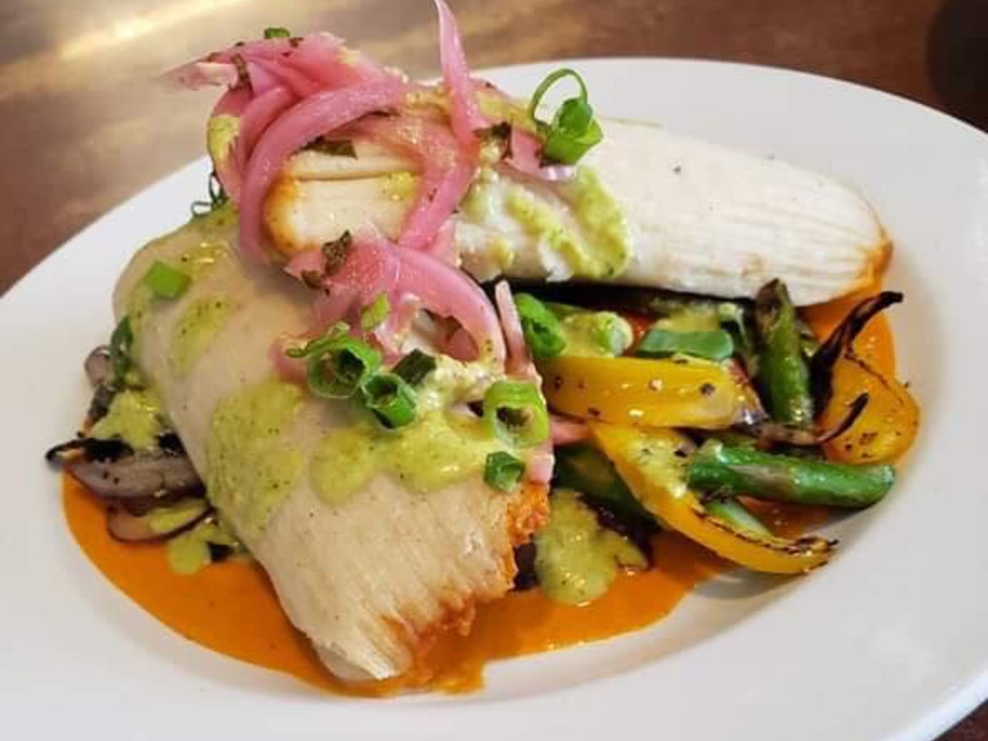 grilled fish with a side of vegetables on a bed of sauce