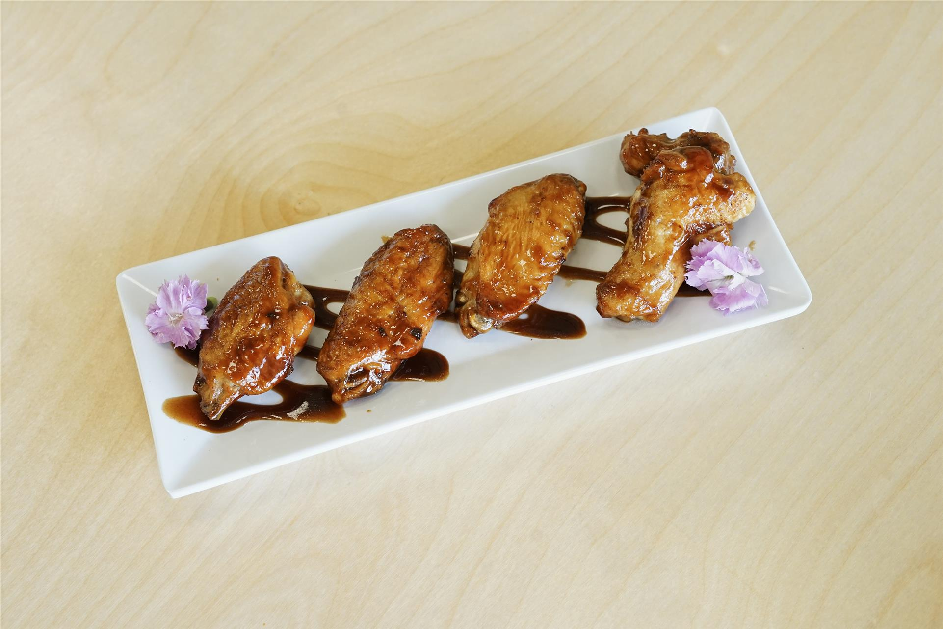 plate of 4 chicken wings with bbq sauce