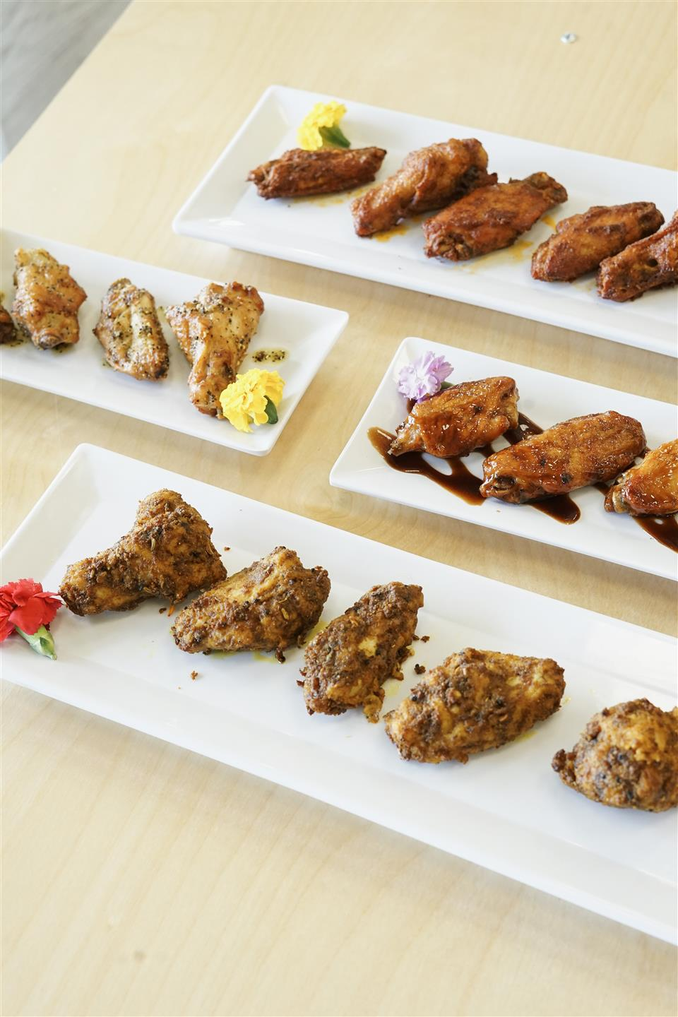 plates of different flavored chicken wings