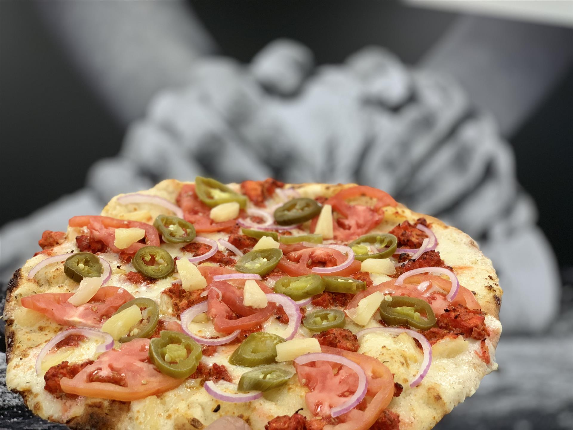 pizza with tomatoes, onions, jalapenos and pineapples