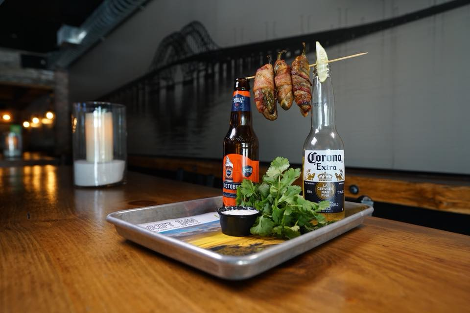 Bacon wrapped jalapeno poppers with two beers in bottles with dipping sauce
