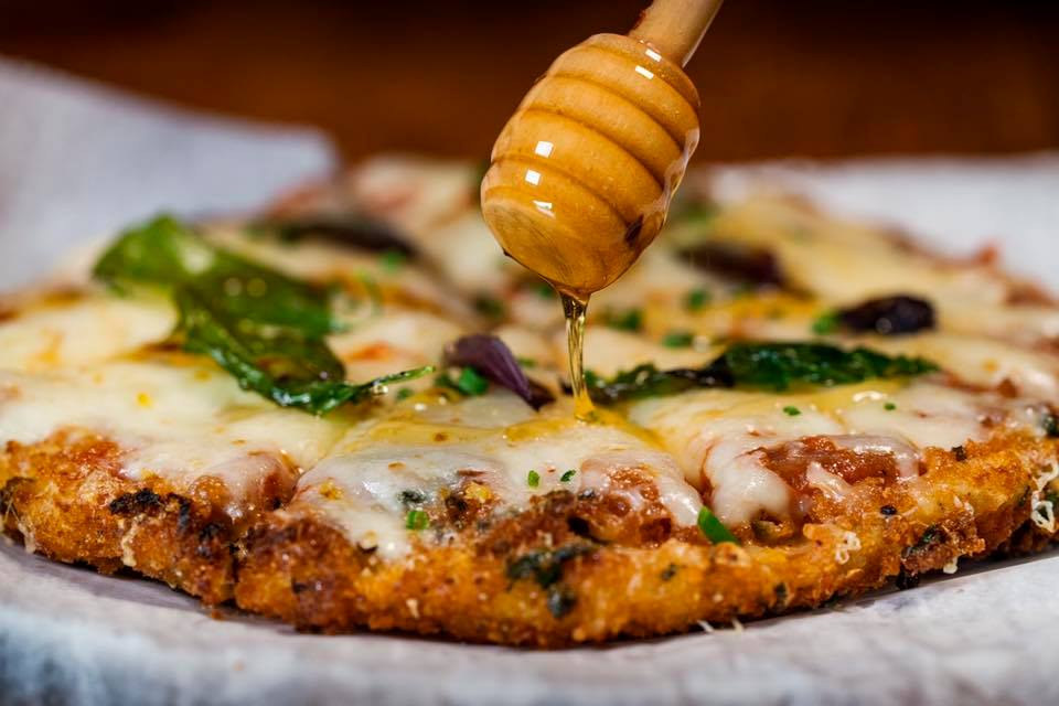 Chicken parm pizza with honey being drizzled