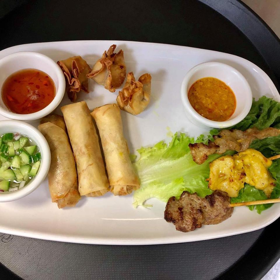 Thai appetizer with fried wontons, spring rolls and chicken, beef and pork Thai satay with assorted dipping sauces