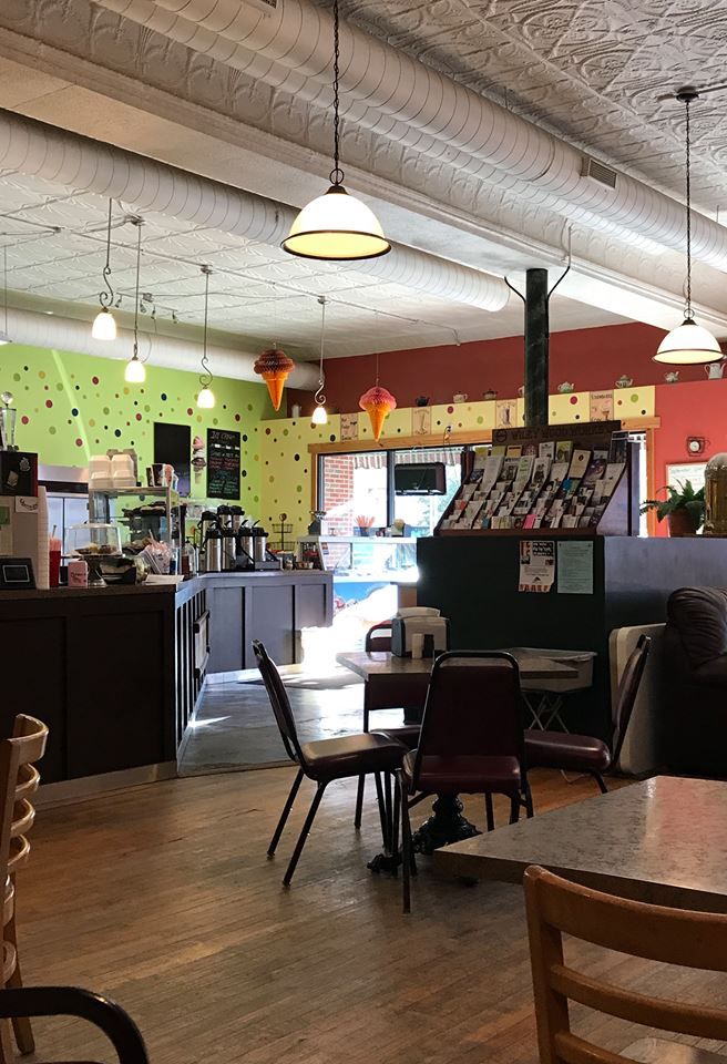 Interior of Evelyn Bay Coffee Shop with tables and chairs and counters with brochures and condiments for coffee