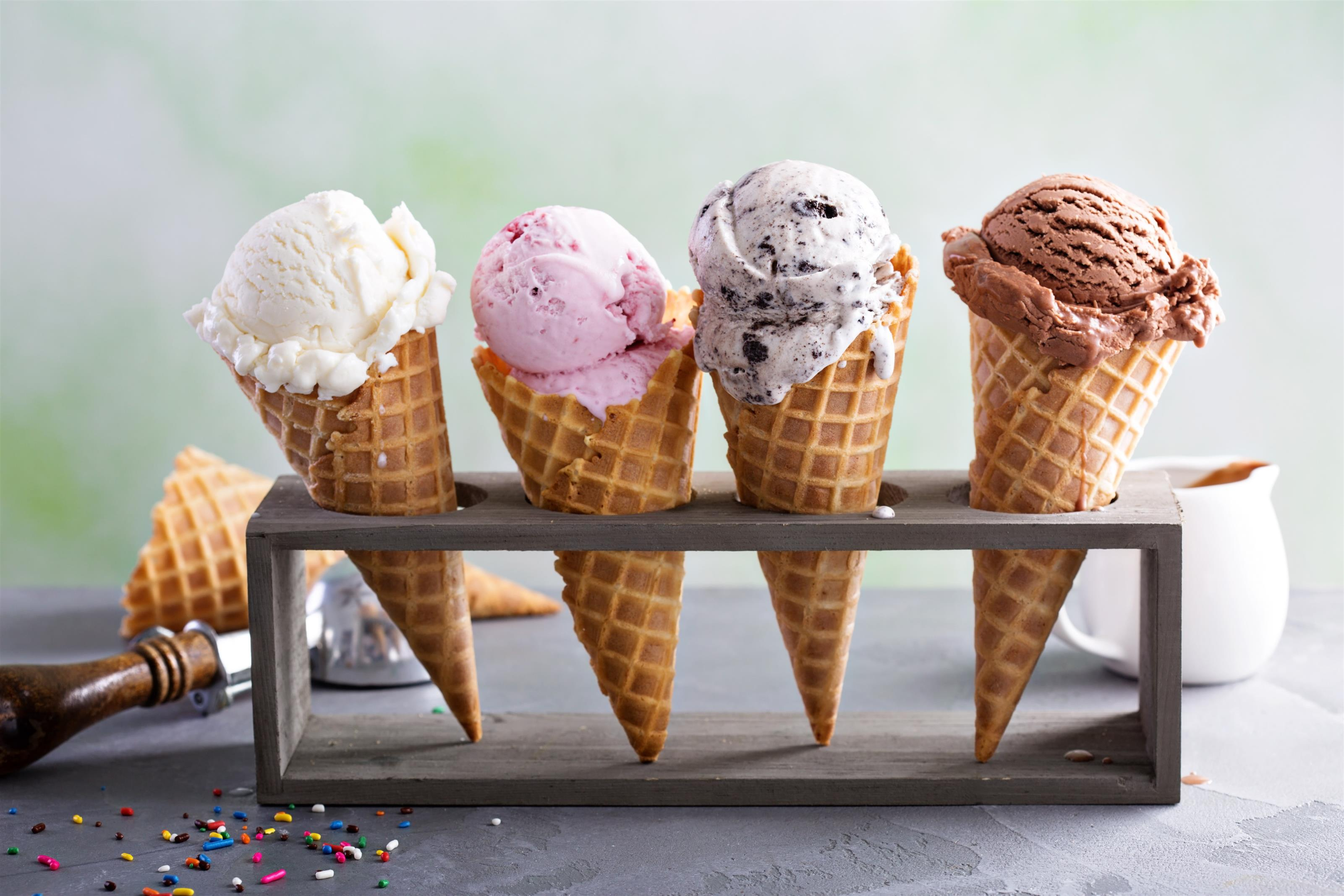 Assorted flavors of ice cream on cones placed in a cone holder