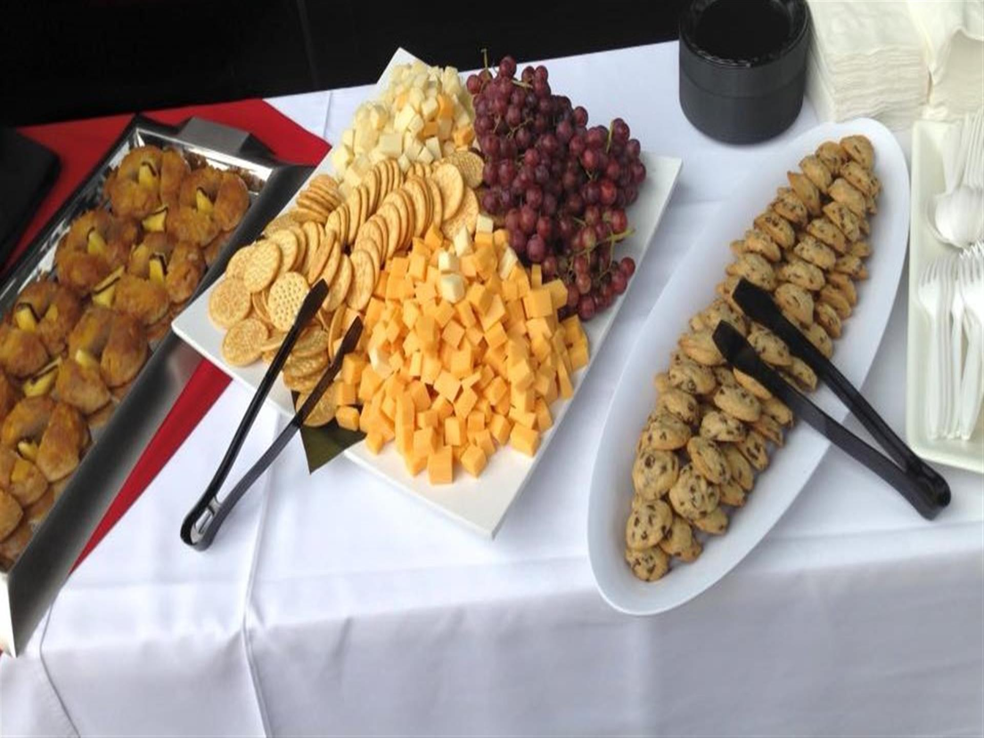 Trays of chocolate chip cookies, crackers, grapes and cheese