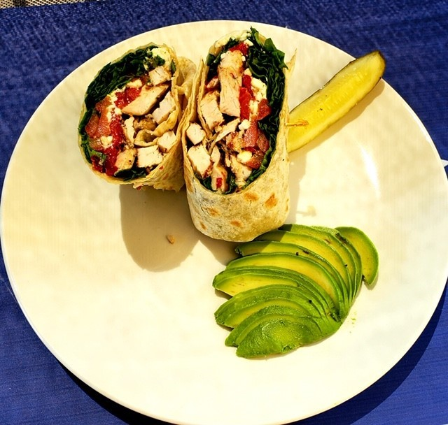 Grilled chicken wrap with lettuce and tomato with a pickle and sliced avocado