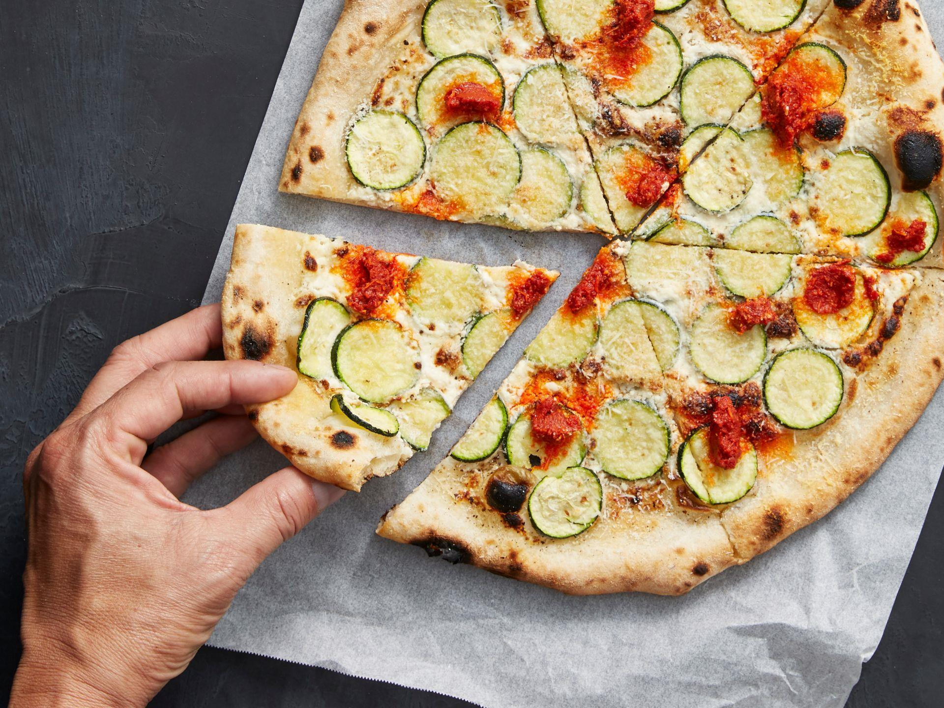 Hand holding a slice of zucchini pizza