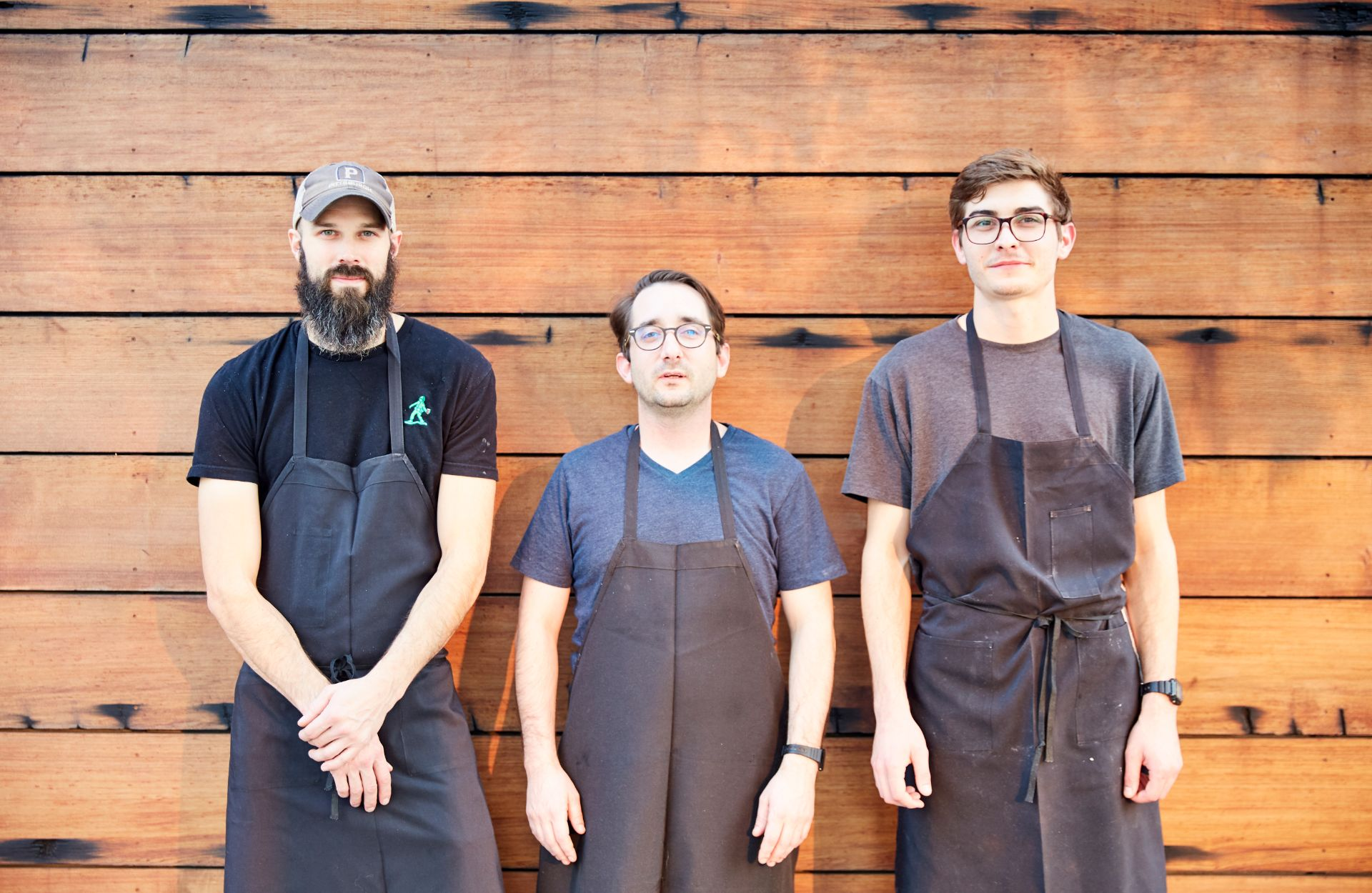 Three chefs wearing aprons posing for a picture in front of a wood wall