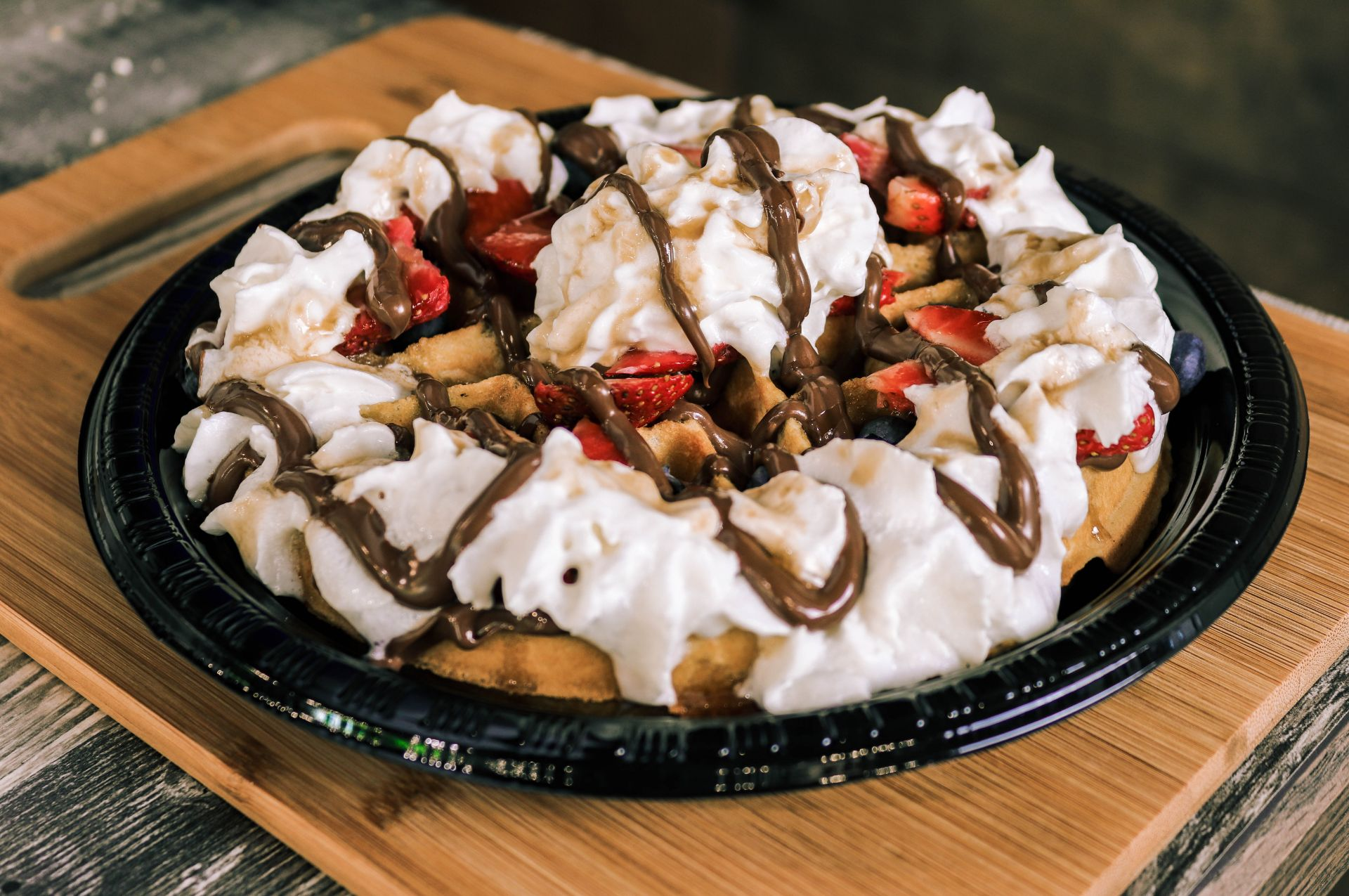 Belgian waffle with whipped cream, fresh fruits and chocolate sauce