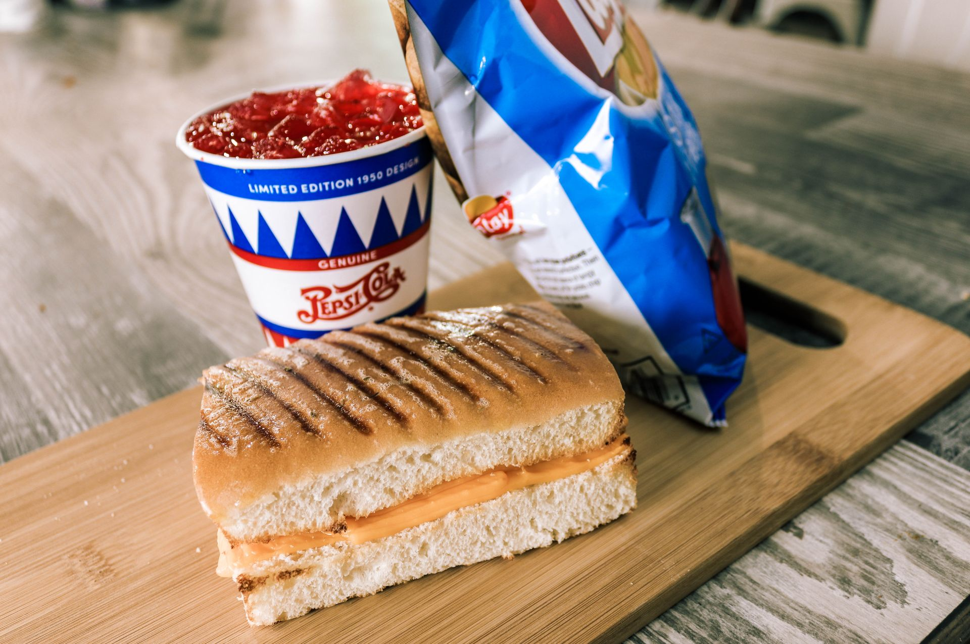 Grilled cheese with fruit punch and a bag of potato chips