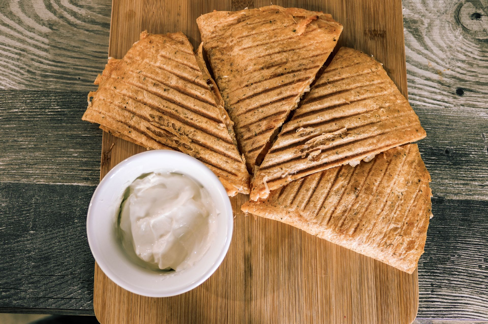 Chicken quesadilla on a wood board with sour cream