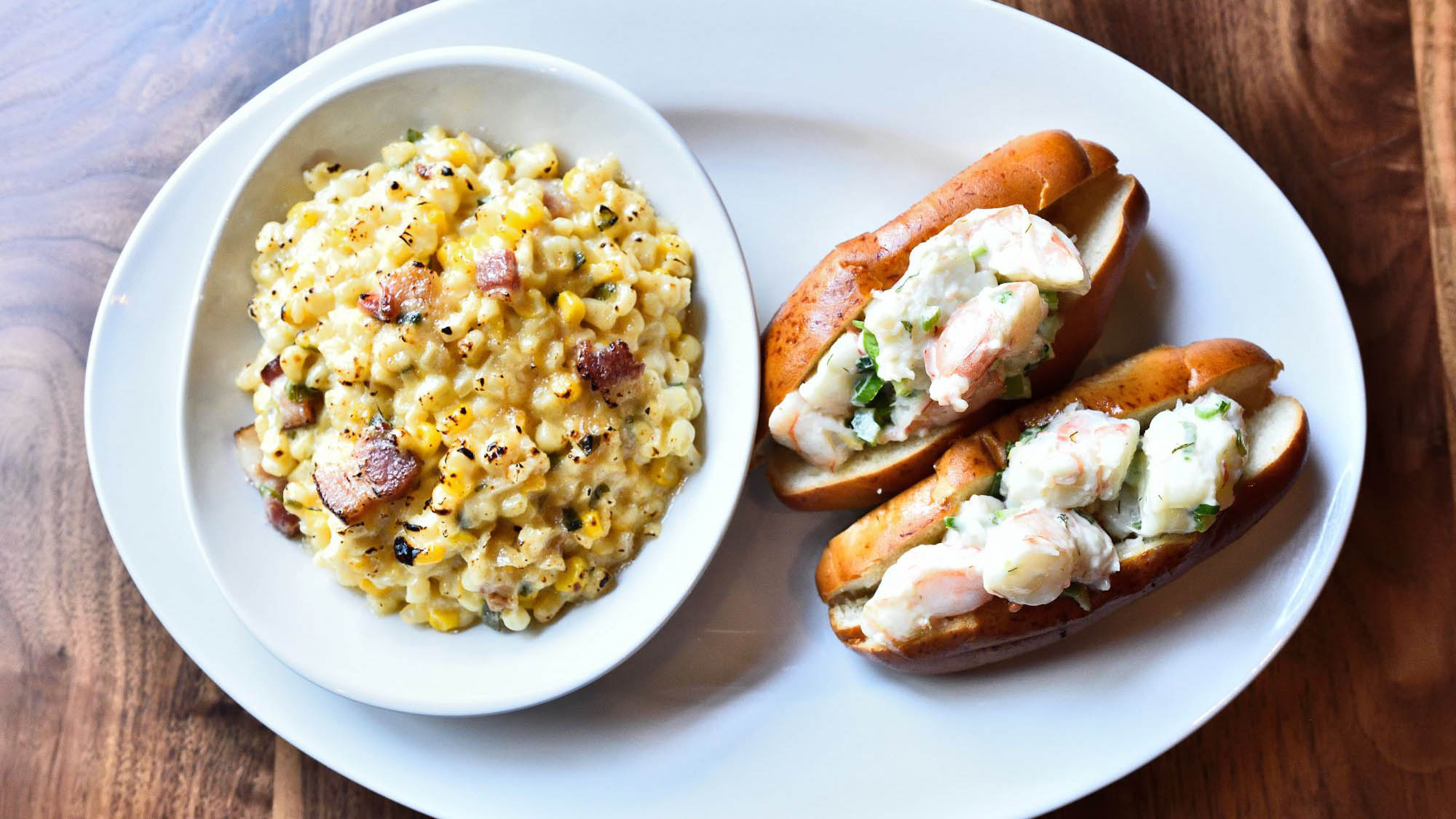 Two lobster rolls on a plate with bacon mac and cheese
