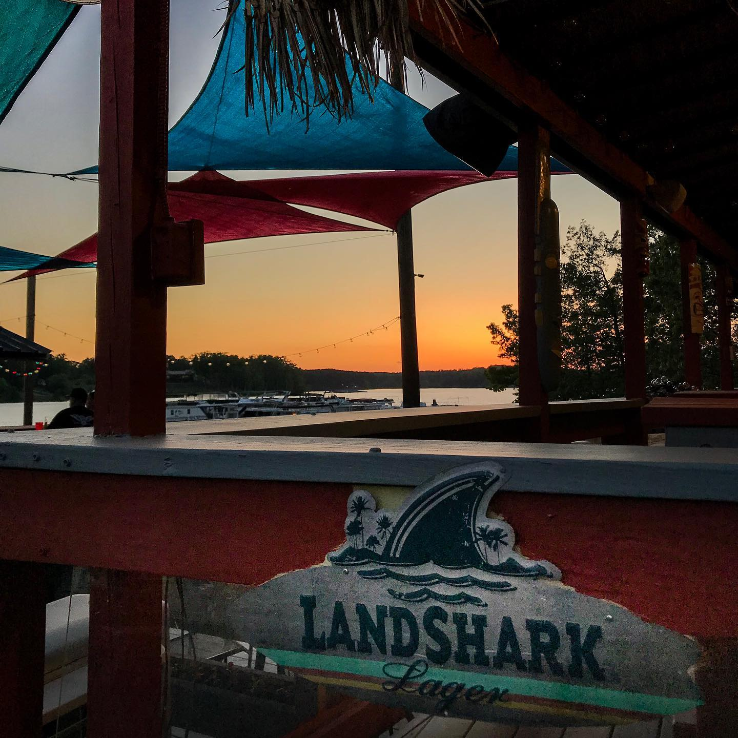 Landshark Lager sign on a banister with a view of a sunset over a lake