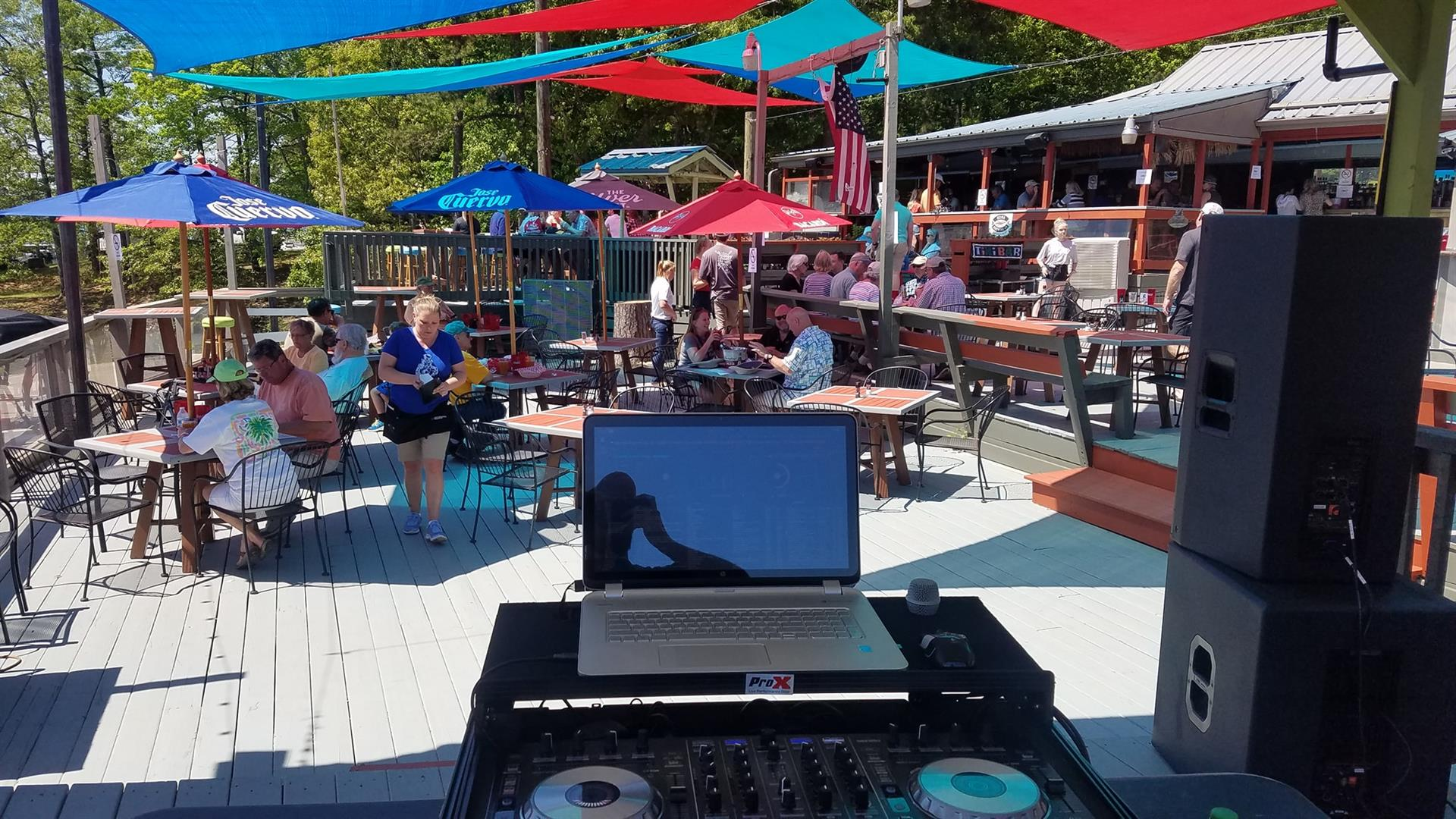 View of a DJ setup on a deck with people sitting at tables under umbrellas