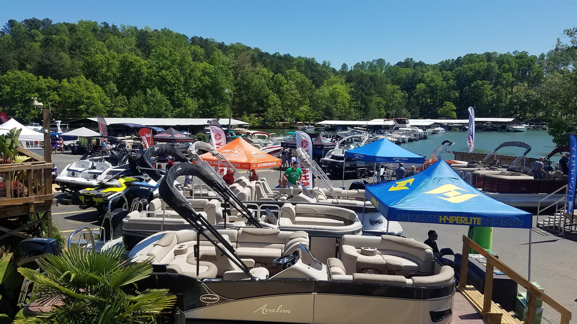 Boats in a parking lot with tents beside a lake