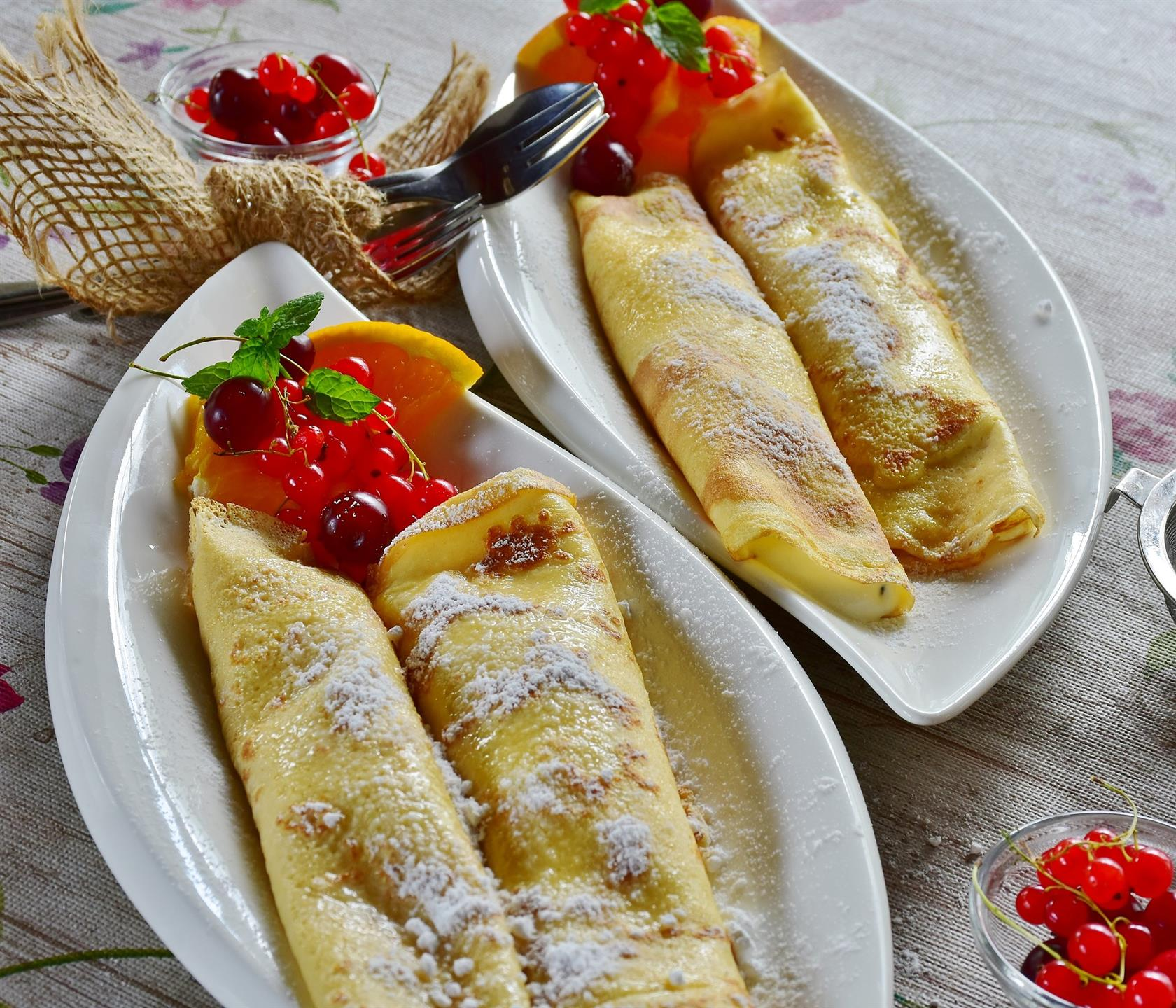 crepes topped with powdered sugar and topped with garnish