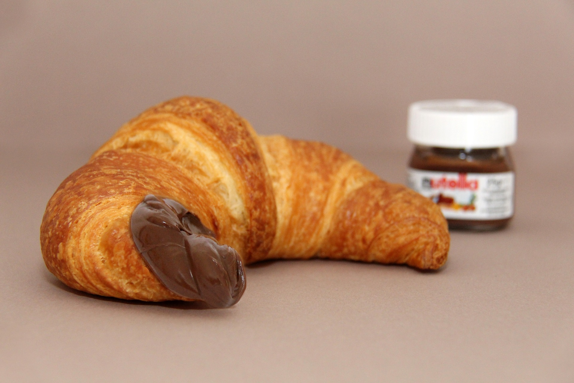 croissant dipped in nutella with a jar of nutella