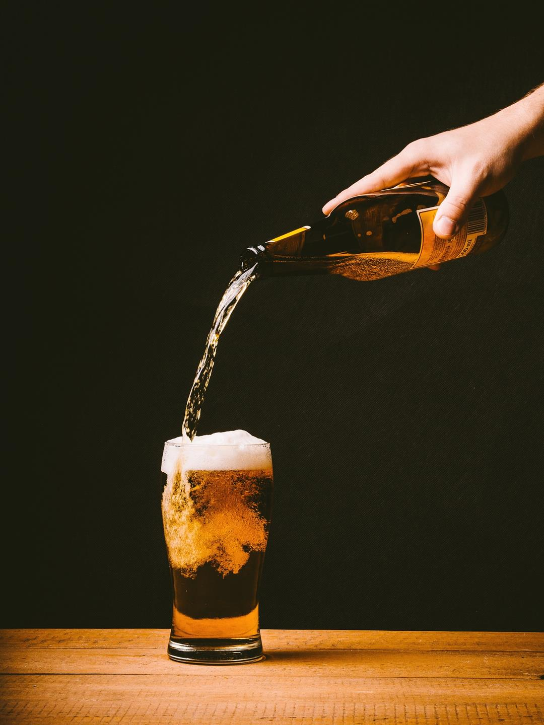hand holding a beer bottle pouring it into a glass