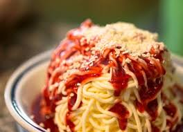spaghetti topped with sauce and sprinkled cheese