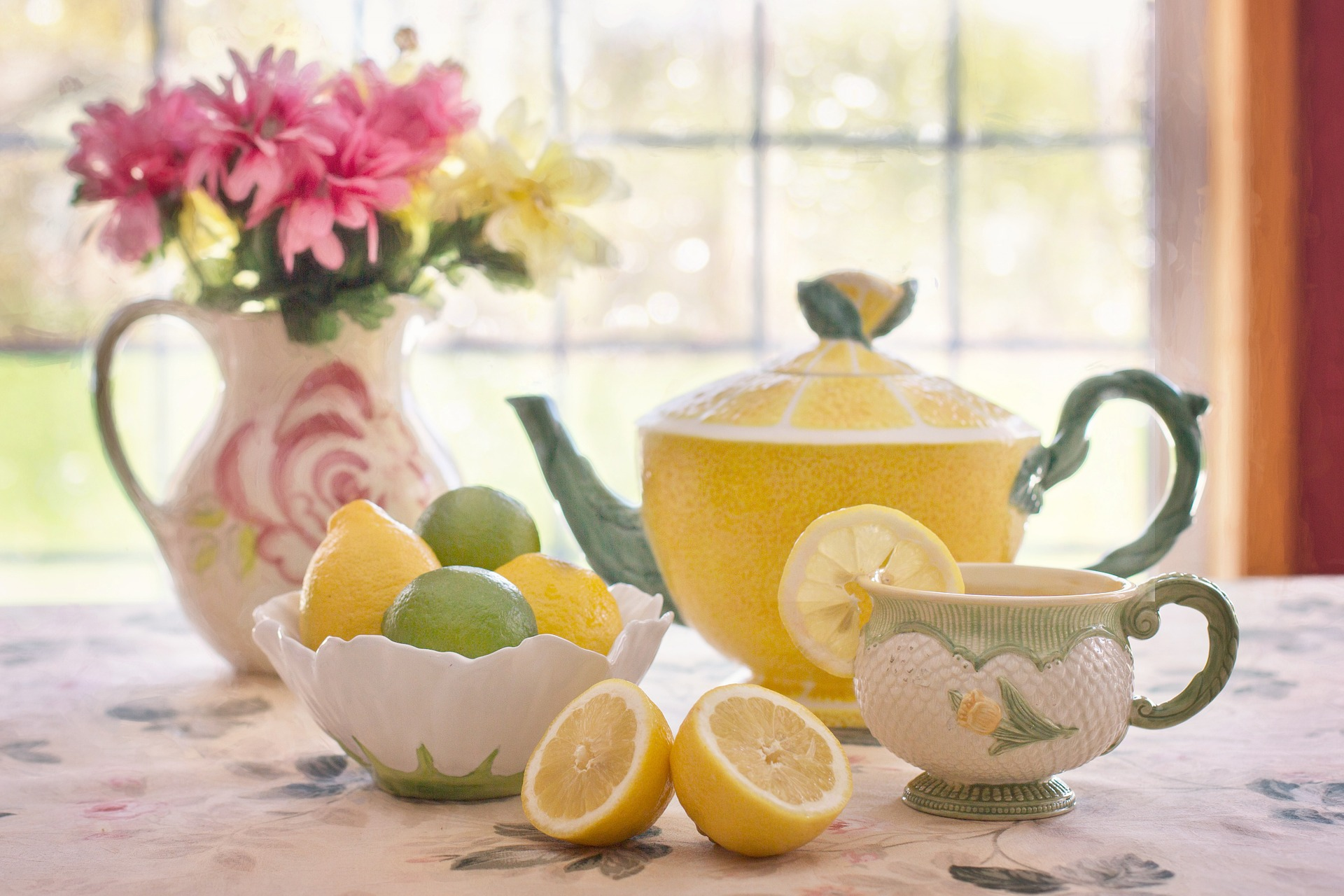 tea pot with lemon and limes in a bowl