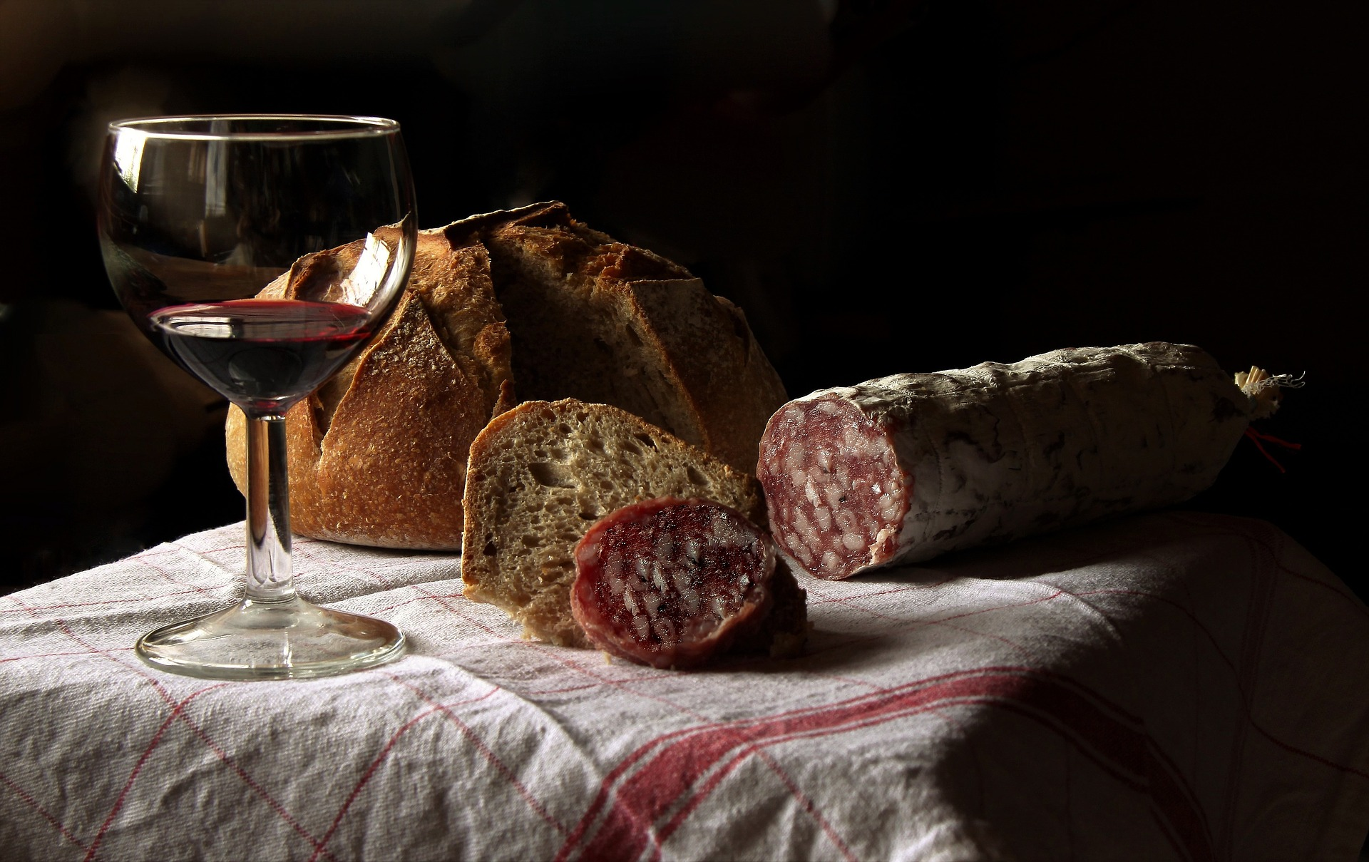 dried salami casing with bread and a glass of wine