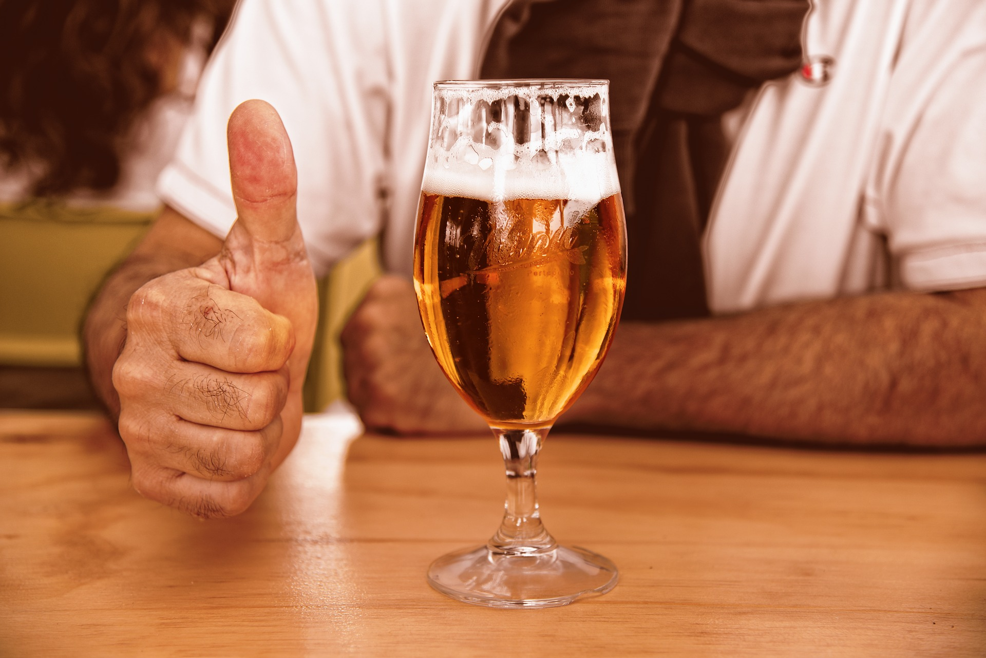 man holding a thumbs up with a glass of beer