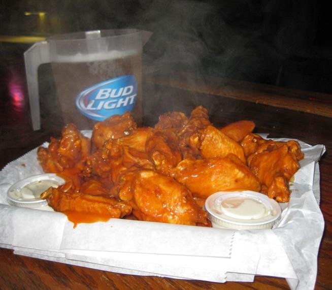 buffalo chicken wings on a platter with a side of blue cheese and a pitcher of bud light