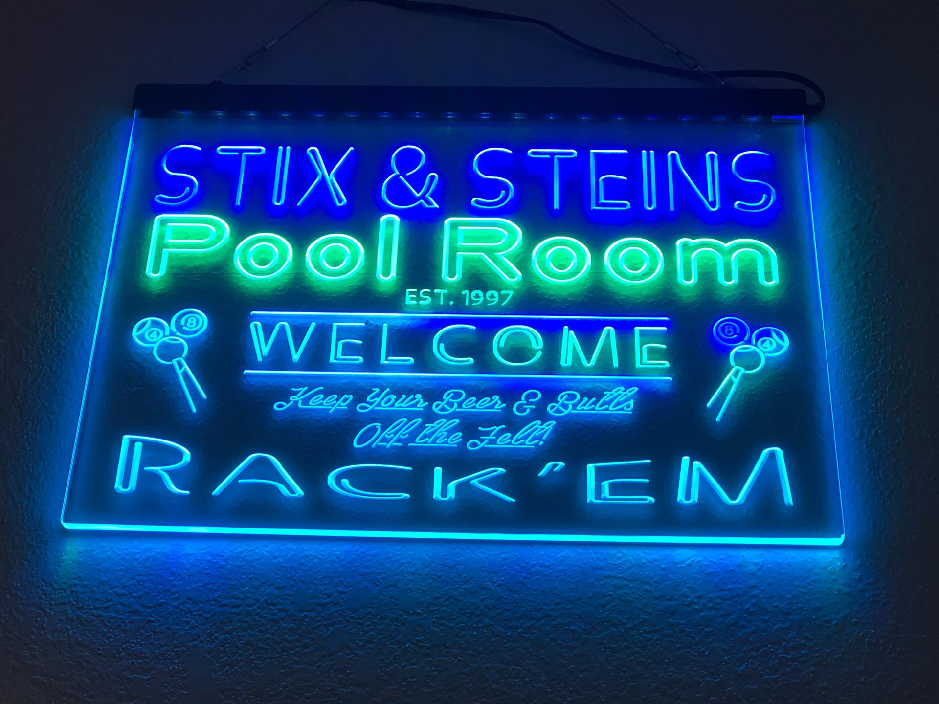 "neon sign that reads ""Stix & Steins Pool Room Est. 1997 Welcome - Keep your Beer and Butts off the felt! Rack'em"