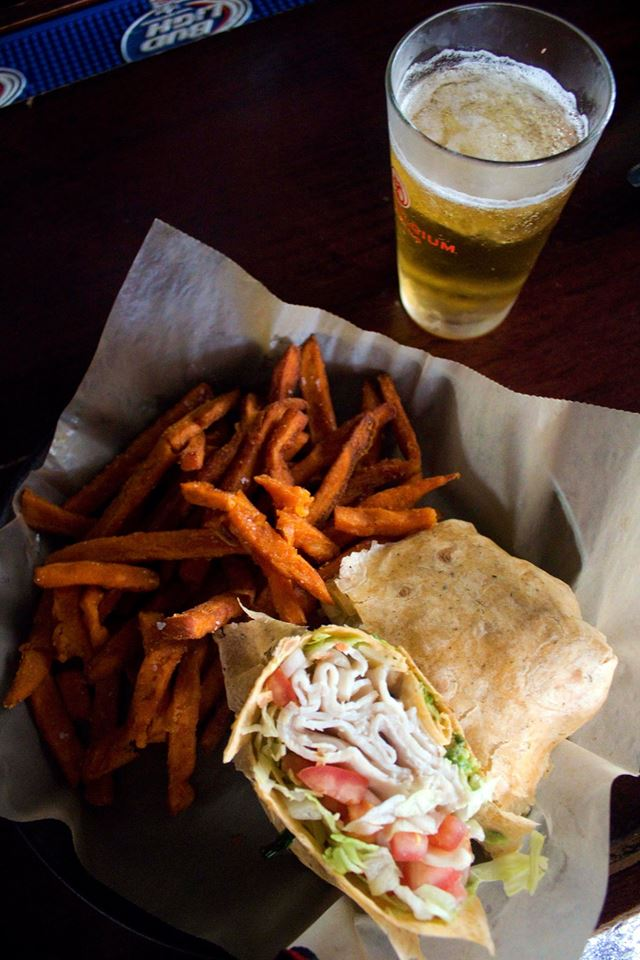 Turkey wrap with lettuce and tomato with a side of sweet potato fries and a beer