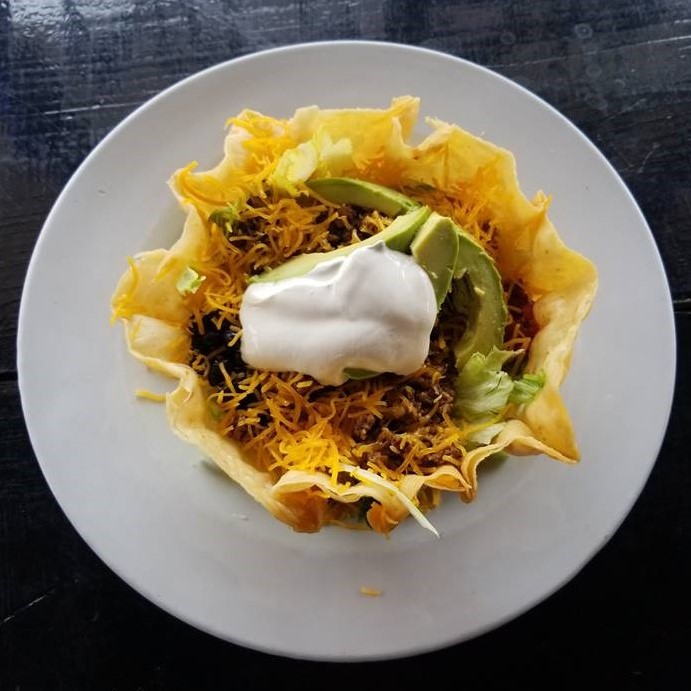 Taco salad in a tortilla bowl with sour cream, avocados and cheese