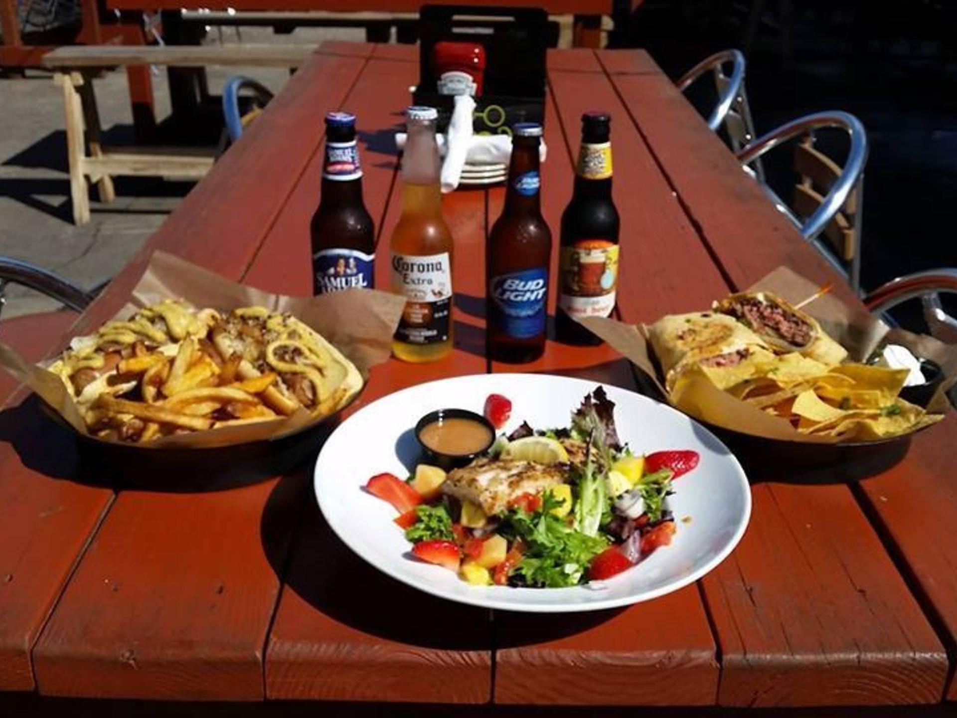Grilled chicken salad, basket of loaded fries with cheese and bacon and nachos on a wooden table with an assortment of bottled beers