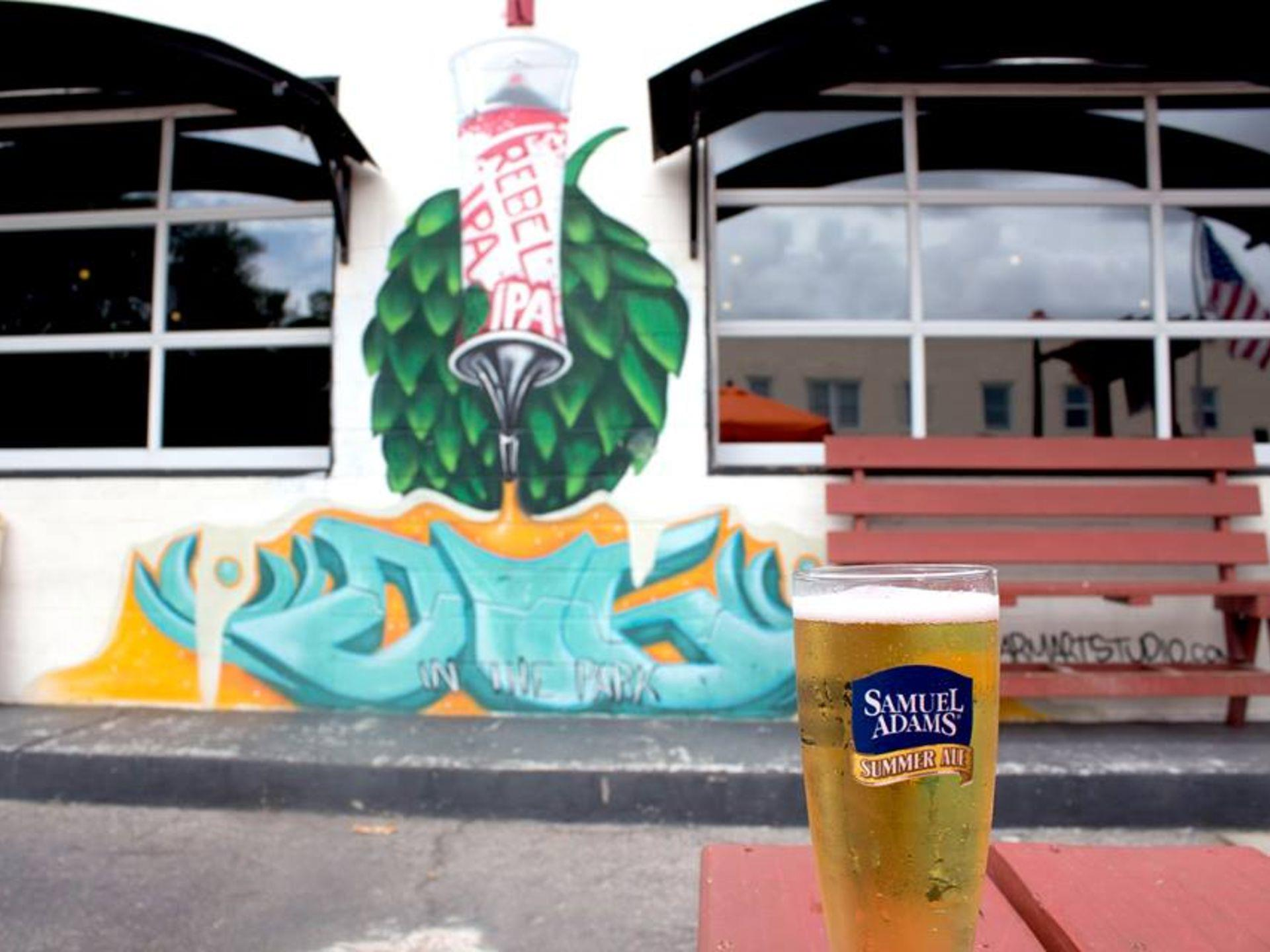 Samuel Adams beer on a table in front of a mural on a wall